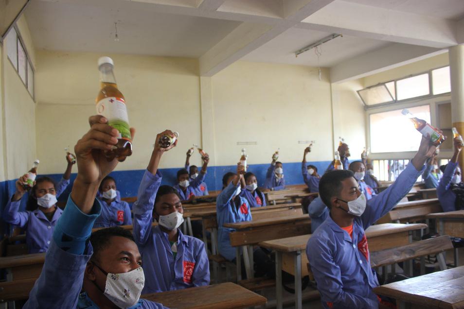 """Madagaskar, Antananarivo: Schüler halten je eine Flasche mit """"Covid Organics"""", die in ihrem Gymnasium in der Hauptstadt Madagaskars verteilt worden waren."""