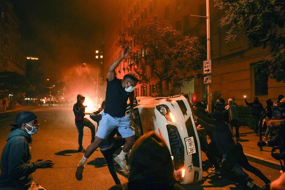 Demonstranten kippen ein am Straßenrand parkendes Auto um und zertrümmern die Autoscheiben.