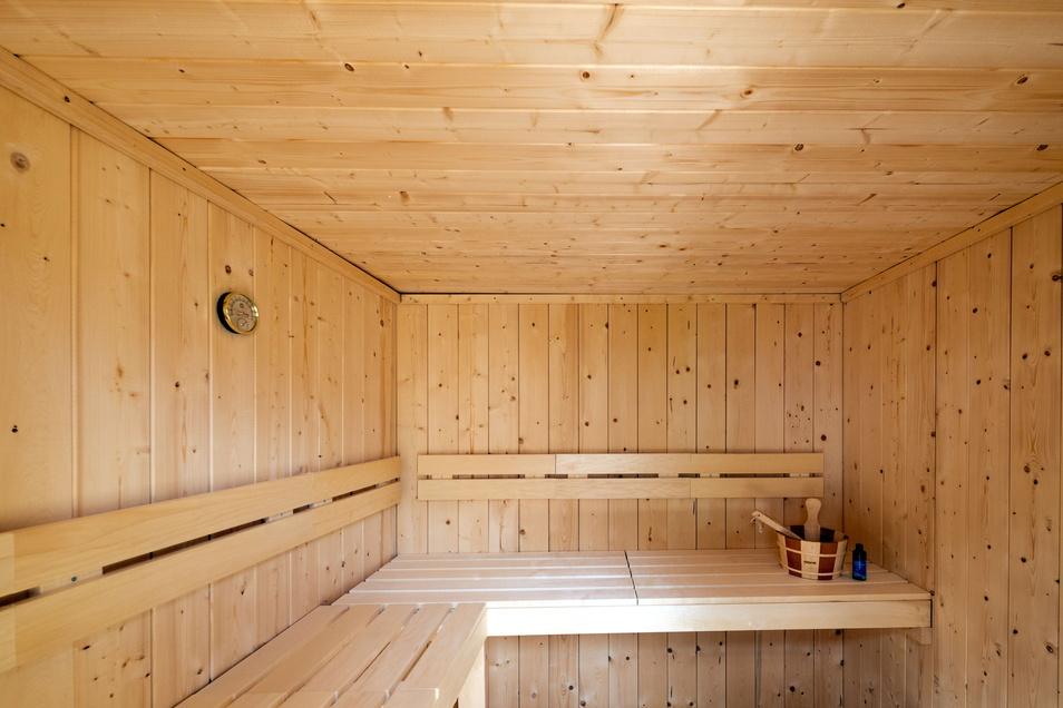 Im Außenbereich befindet sich eine Sauna mit einer angrenzenden Dusche.