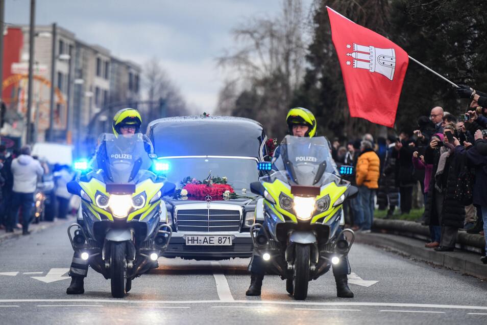 Letztes Polizei-Geleit für Jan Fedder: Nach der Trauerfeier für den Schauspieler wird der Wagen mit seinem Sarg bei der Fahrt durch die Stadt von einer Motorradeskorte begleitet.