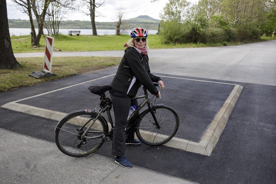 Stadträtin Yvonne Reich steht mit ihrem Fahrrad in Deutsch Ossig an einem der sechs neuen Huckel am Rundweg um den Berzdorfer See. Hier war sie gestürzt. Nun reagiert das Rathaus auf die Gefährlichkeit der Huckel.