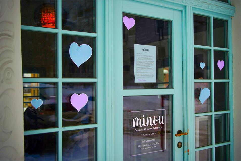 Die Tür zum Kaffeehaus haben Unbekannte mit bunten Herzchen beklebt.