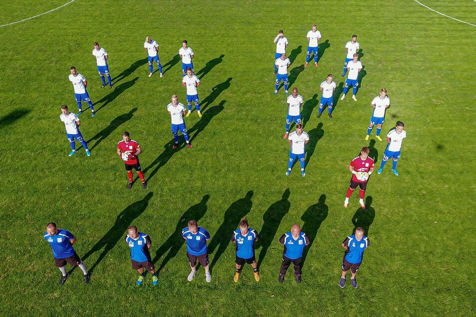 Auf Abstand stehen Spieler, Trainer und Betreuer des Bischofswerdaer FV für das Mannschaftsfoto.