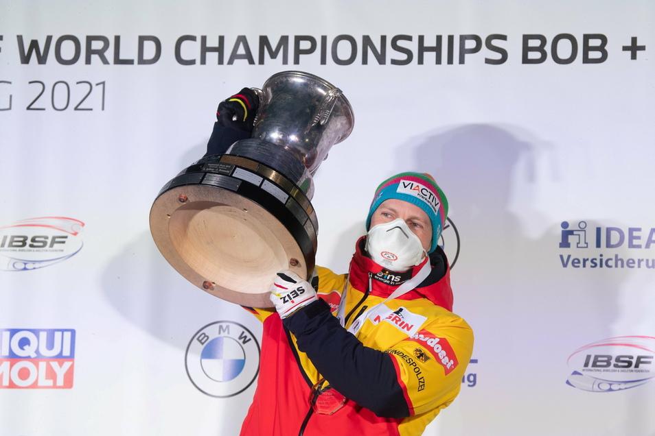 Die Trophäe, die inzwischen fast seine eigene ist: Francesco Friedrich präsentiert den WM-Pokal, auf dem die Namen aller Zweierweltmeister verewigt sind. Seit 2013 ist es immer wieder seiner.