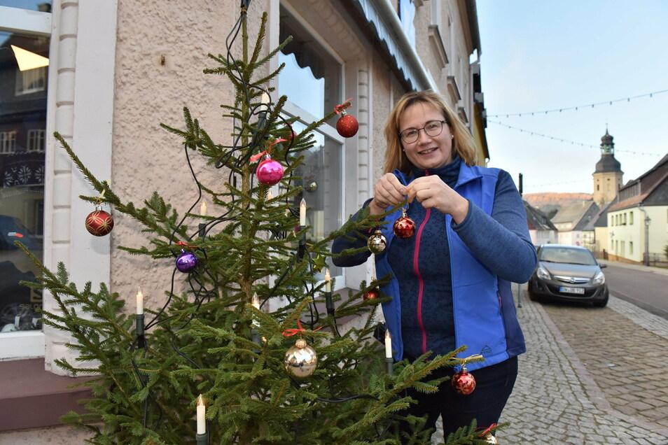 Katrin Lohse vom Geisinger Sportgeschäft schmückt bereits den Weihnachtsbaum vor dem laden auf der Hauptstraße.