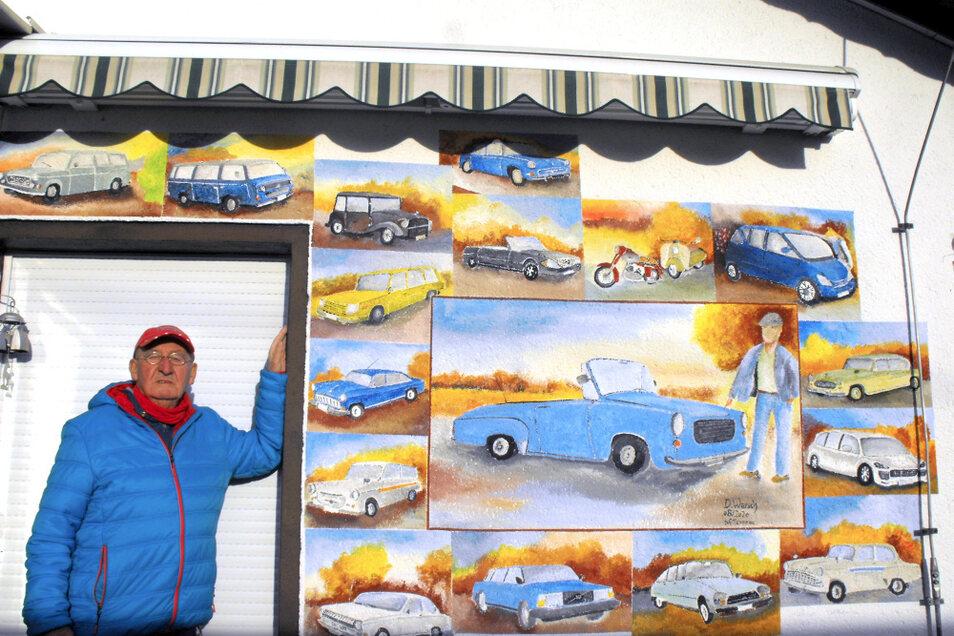 Werner Hantschke vor seiner Autowand mit Porträts all der Modelle, die er bisher gefahren hat. Den größten Teil und zentralen Platz nimmt natürlich der himmelblaue Wartburg 312/300 HT ein – aber auch Trabant P 50 Kombi, Škoda Octavia, Sachsenring,