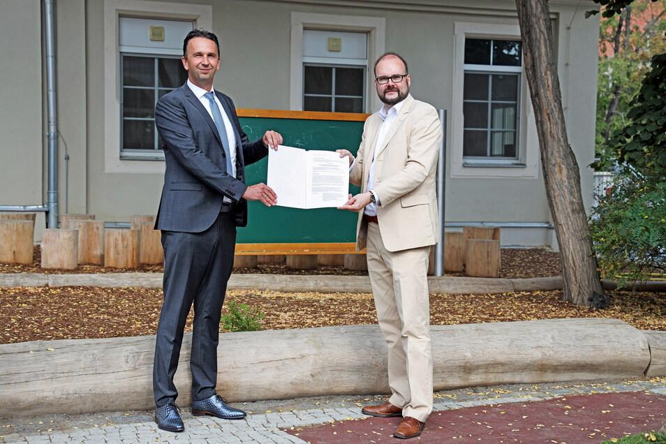 Vor fast einem Jahr überreichte Sachsens Kultusminister Christian Piwarz (CDU, r.) Riesas OB Marco Müller (CDU) den Förderbescheid - jetzt wurden gleich eine ganze Reihe Investitionen beschlossen.