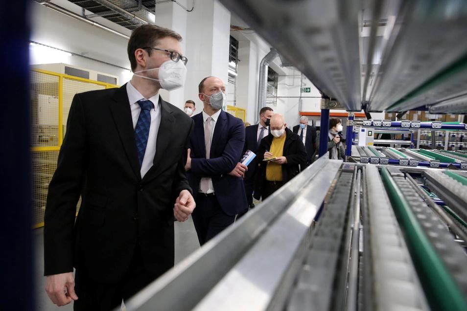Dr. Sebastian Pohlmann (vorn), Vizepräsident für Innovation bei Skeleton, erklärt dem Ostbeauftragten der Bundesregierung, Marco Wanderwitz (Mitte), die Produktion von Batteriezellen in Großröhrsdorf.