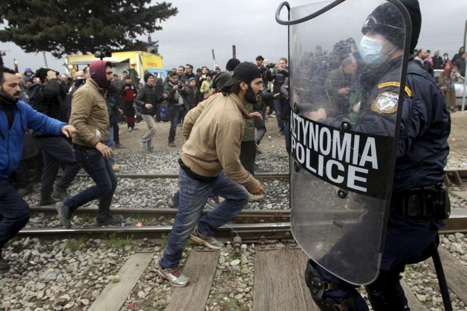 Griechische Polizisten wollen in Idomeni den Sturm der Flüchtlinge stoppen.