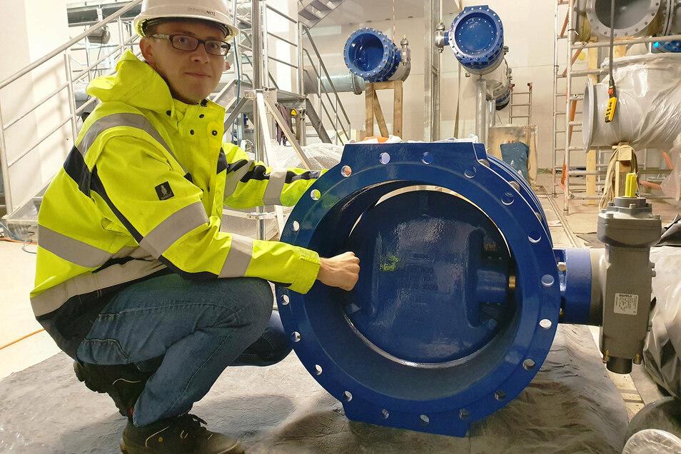 Drewag-Projektleiter Martin Kayser zeigt eine eingebaute Absperrarmatur im Technikgebäude. Die Absperrklappe ist 60 Zentimeter hoch.