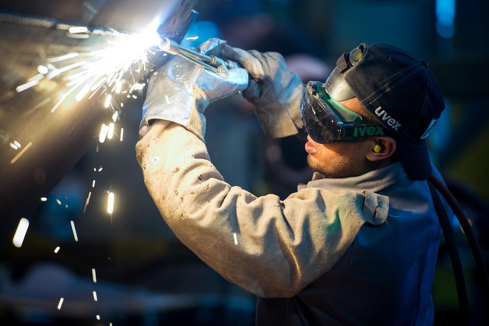 Ein zugewanderter Schweißer arbeitet an einem Stahlsegment für einen Windradturm.