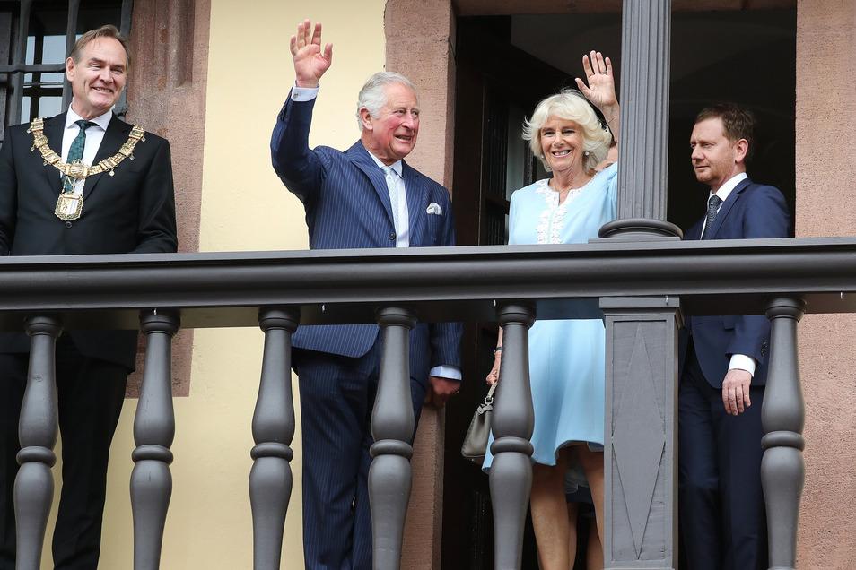 Der britische Thronfolger Prinz Charles und seine Ehefrau Camilla (M) stehen mit Burkhard Jung (l), Bürgermeister von Leipzig, und und Michael Kretschmer (CDU, r), Ministerpräsident von Sachsen, auf dem Balkon des Rathauses.