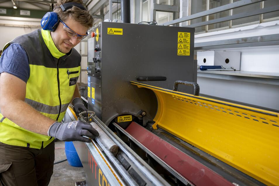 Robert Zimmermann vom Helmholtz-Institut Freiberg für Ressourcentechnologie bereitet die Bohrkerne für die hyperspektralen Untersuchungen vor. Um zwei glatte Hälften zu bekommen, zersägt er sie in die Hälfte.