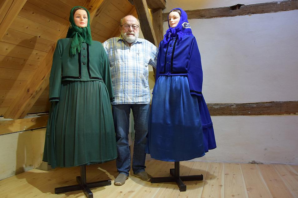 Hans Groba auf der erweiterten Galerie mit zwei Figurinen, die die winterliche Ausgehtracht tragen.