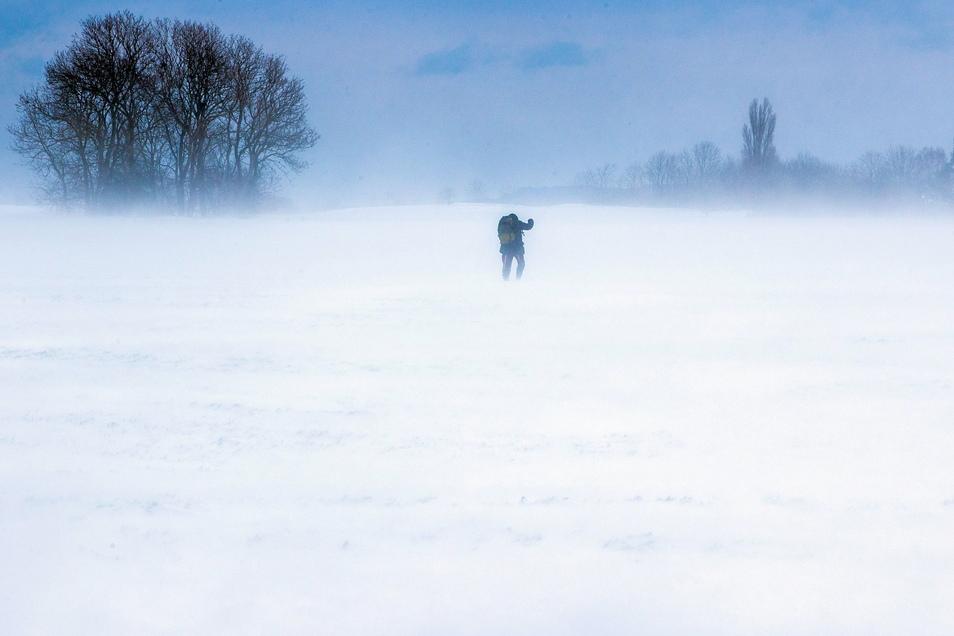 Mecklenburg-Vorpommern, Putgarten: Ein Mann läuft ü·ber einen verschneiten Acker auf der Insel R·ügen.