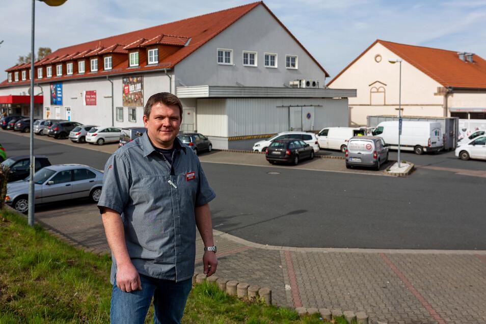 Marktleiter Michael Wolf steht vor dem bisherigen Rewe-Markt hinter ihm und der neuen Getränkeabteilung rechts davon, die gerade eingerichtet wird.