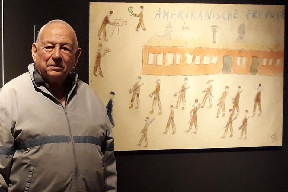 Thomas Geve steht neben einer vergrößerten Zeichnung während einer Ausstellung.