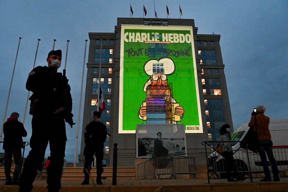 Karikaturen der französischen Satirezeitung Charlie Hebdo werden auf die Fassade eines Hauses projeziert.