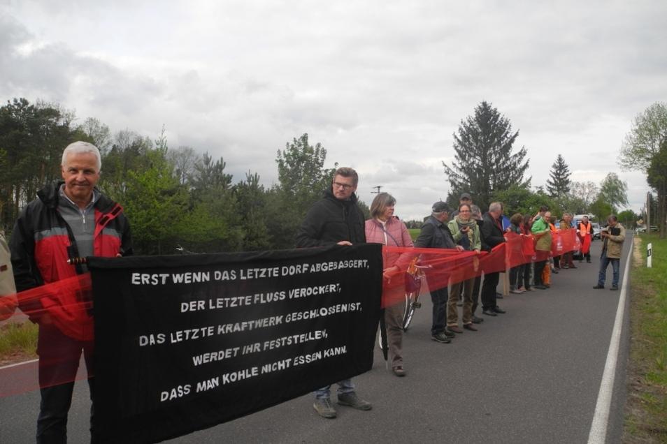 Mit einem symbolischen roten 80 Meter langen Band entlang der Straße Schleife-Mühlrose demonstrierten die Teilnehmer für wirksamen Schutz der Orte im Schleifer Kirchspiel vor Lärm, Staub und Rutschungsgefahren.