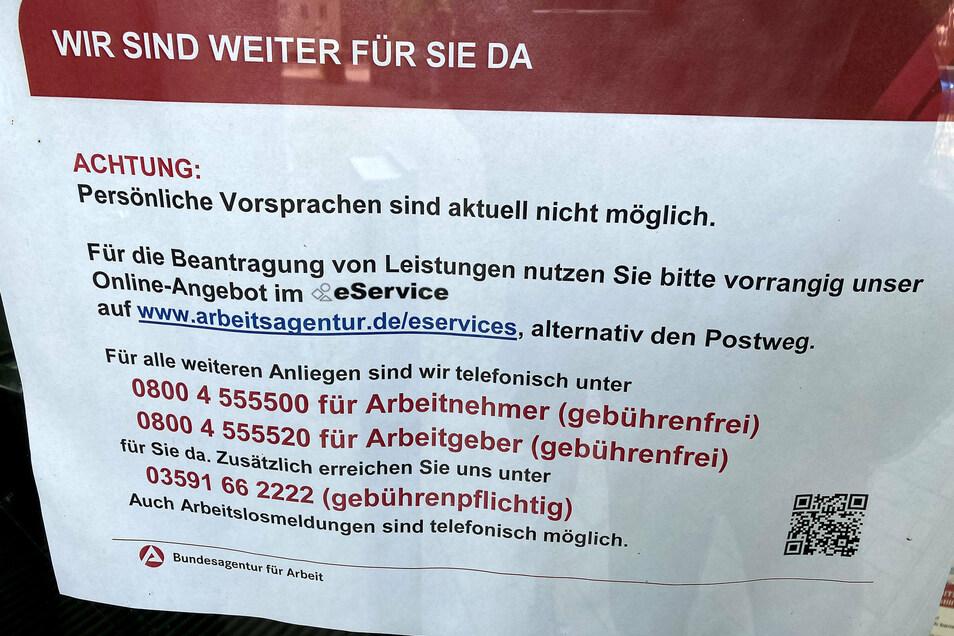 Wir sind weiter für Sie da: Zettel an der Drehtür zur Arbeitsagentur in der Zittauer Kantstraße.