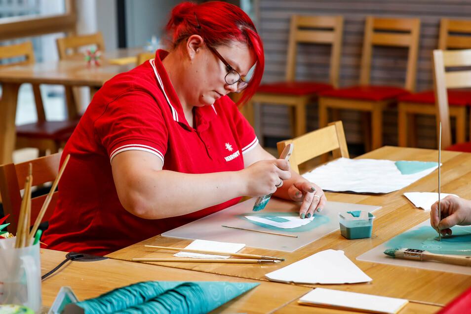 Jenny Bryla streicht die Zacken akurat mit dem mintfarbenen Kleister ein.