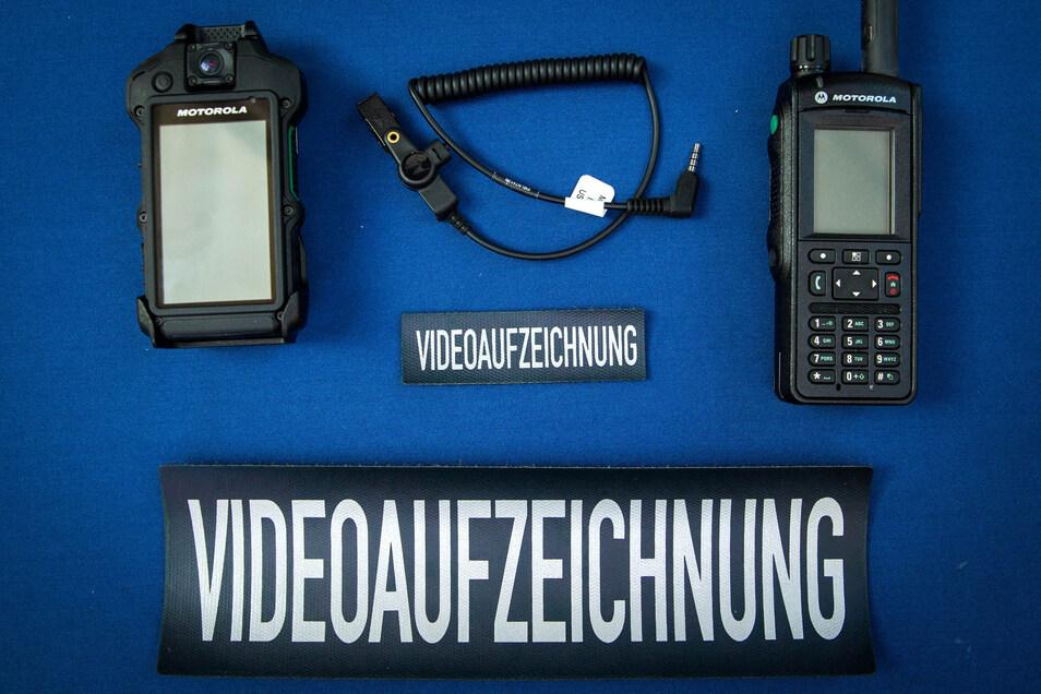 Video-Polizisten sind durch Schriftzüge an der Uniform weithin zu erkennen. Die Motorola-Kamera (l.) kann das Funkgerät des gleichen Herstellers steuern.