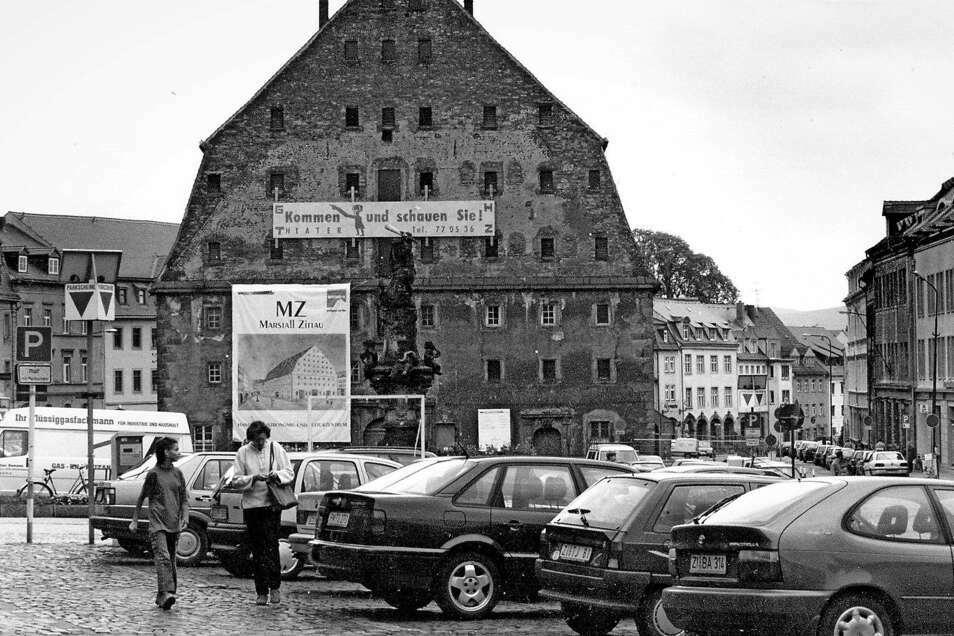 """Das Salzhaus vor der Sanierung in den 1990er Jahren. Auf dem Banner links wurde damals für den """"Marstall Zittau"""" geworben. Als Blickfang fällt je ein Sims als Traufkante an den Giebelseiten auf."""