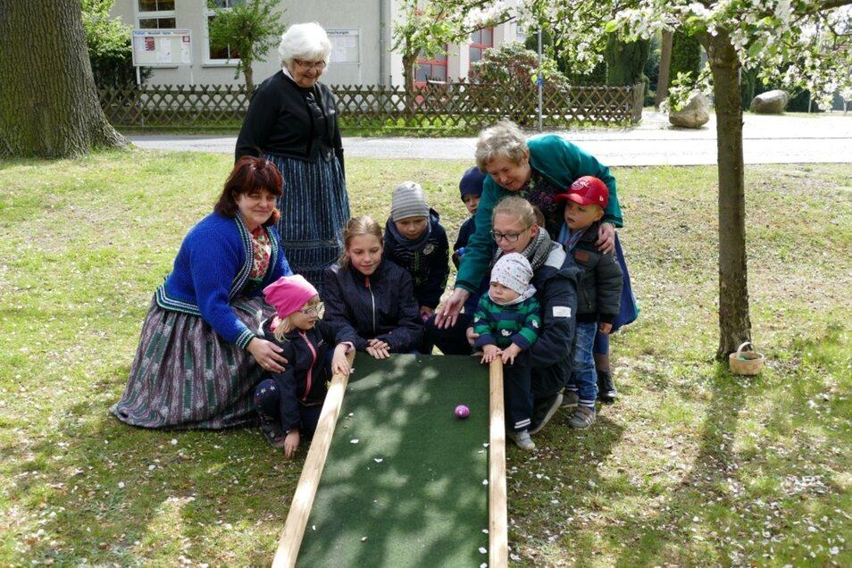 Unter dem blühenden Apfelbaum war die Rutsche. Die Kinder folgten genau den Erklärungen der sorbischen Frauen zum Ritual des Waleiens.