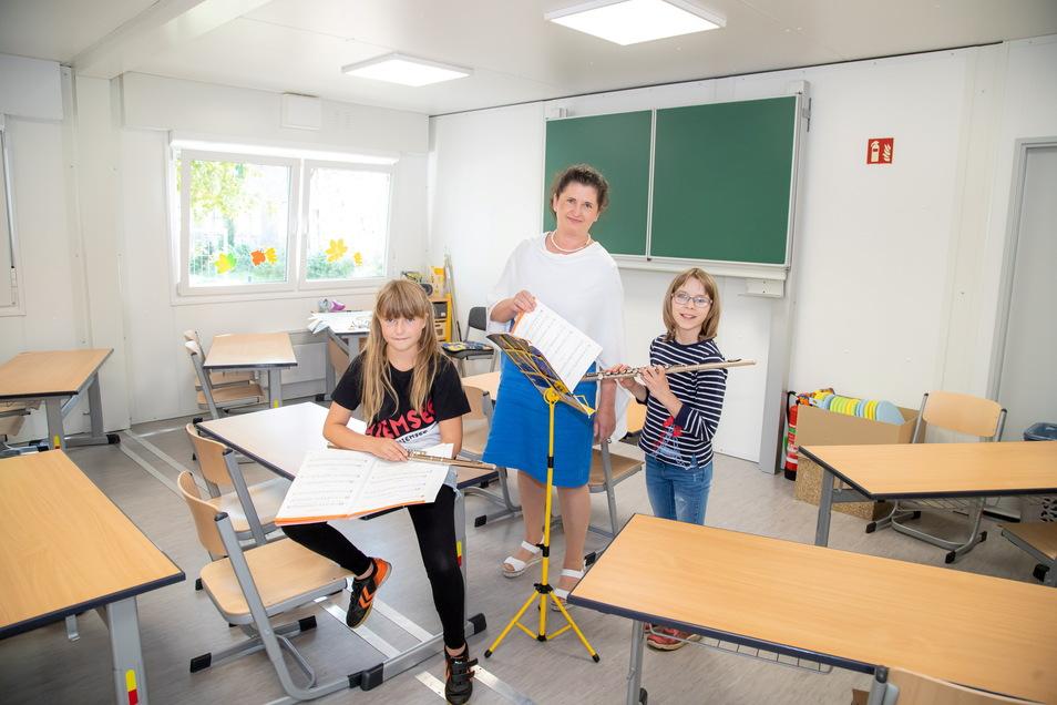 Finnya und Sarah proben im neuen Unterrichtsraum mit der Querflöte für das Programm zur Einschulung. Schulleiterin Steffi Miethe (Bildmitte) freut sich über den zusätzlichen Platz.