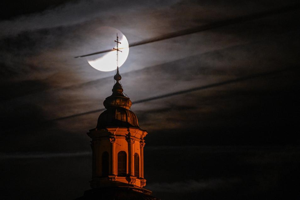 Der teils verdeckte Mond ist hinter Basilika in Weingarten zu sehen, während ein Flugzeug vor dem Mond vorbei fliegt.