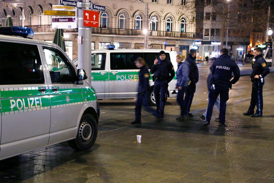 Polizisten stehen in der Nacht zum Sonnabend am Tatort am Augsburger Königsplatz . Dort war ein 49 Jahre alter Feuerwehrmann bei einer Auseinandersetzung mit Jugendlichen getötet worden.