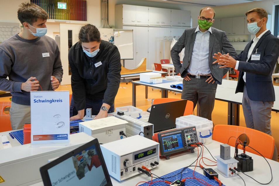 Schüler aus Riesa untersuchen den elektrischen Schwingkreis, Kultusminister Christian Piwarz (2.v.r.) schaut zu. Links Radoslav Vanko.