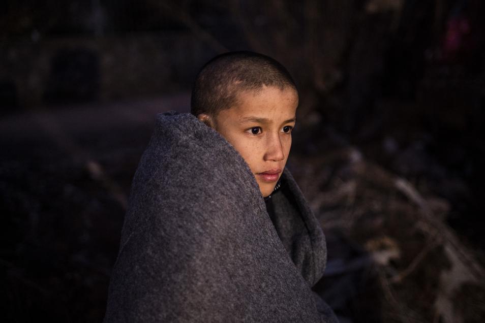Ein Junge sitzt in Decken eingewickelt am Strand des Dorfes Skala Sikamias auf Lesbos, nachdem er mit einem Beiboot die Ägäis von der Türkei aus überquert hat.