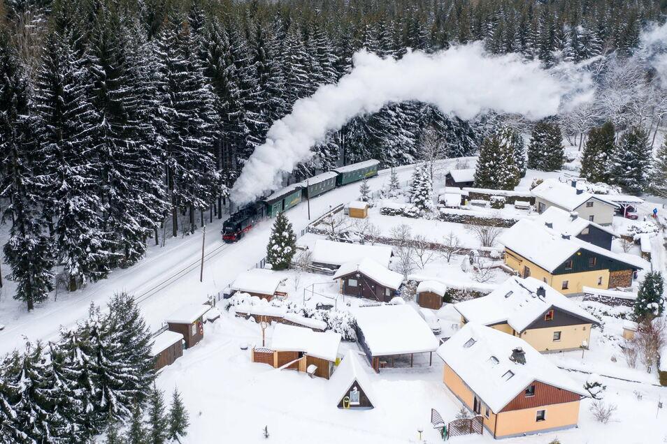 Die Fichtelbergbahn dampft durch das verschneite Erzgebirge. Den Passagieren bietet sich momentan ein wundervoller Ausblick auf verschneite Landschaft.