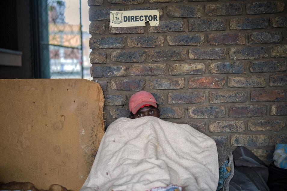 Südafrika, Pretoria: Ein Mann liegt unter einer Decke, nachdem er und andere Obdachlose von der Polizei in die Sportanlage Caledonian Stadium gebracht wurden. In Südafrika wurde eine 21-tägige Ausgangssperre eingeführt, in Reaktion gegen die Ausbreitung d