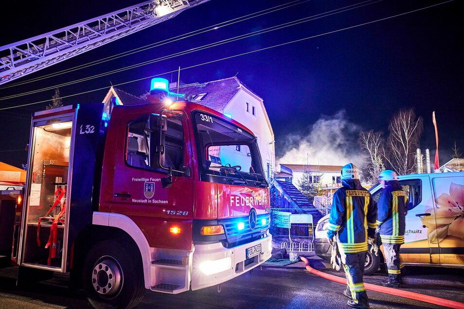 Silvester, nachmittags. Feuerwehrleute löschen den Brand in der Gärtnerei Gruschwitz in Langburkersdorf.