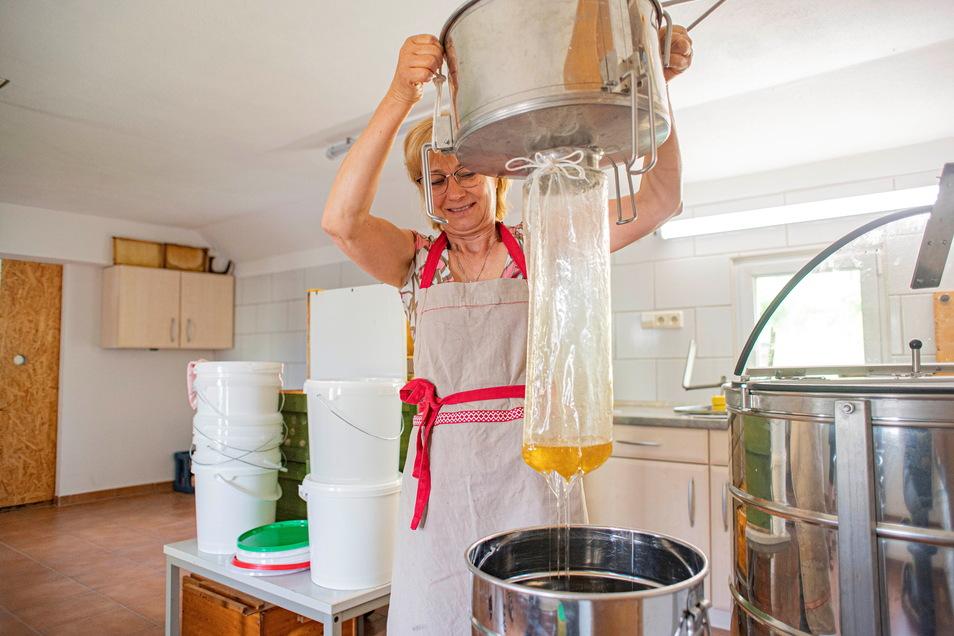 Beate Wendt filtriert mit Hilfe dieses Feinsiebes die letzten Schwebeteilchen aus dem Honig.