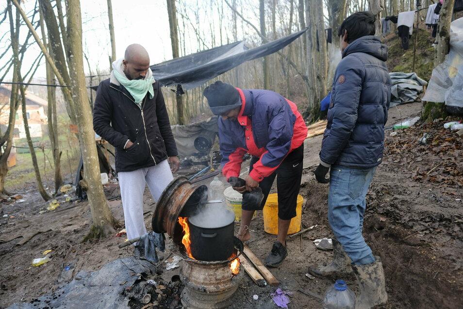 Migranten kochen auf einem aus Radfelgen gebauten Herd in einem provisorischen Lager