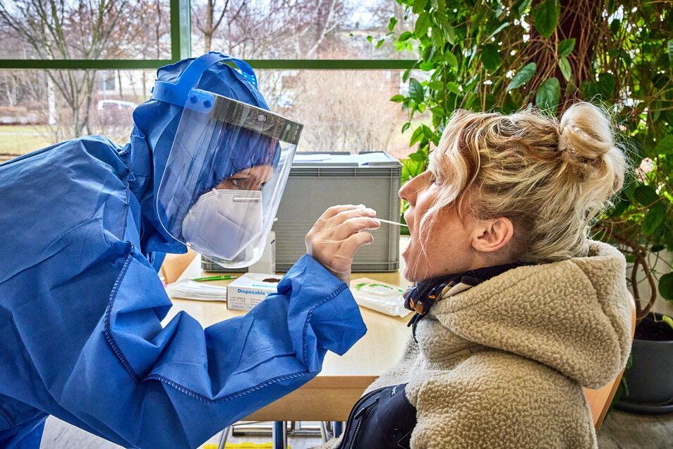 Einmal Mund auf, bitte: Kathleen Molnar (rechts) aus Sebnitz lässt sich im Sportforum Neustadt kostenlos auf das Corona-Virus testen.