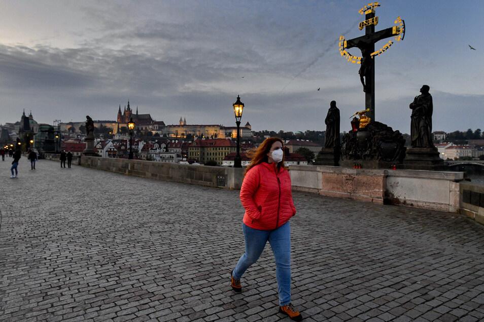 Eine Frau mit Mund-Nasen-Schutz geht über die Prager Karlsbrücke.