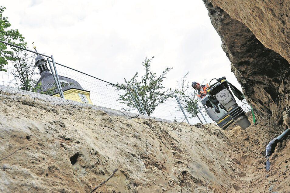 Die Verlegung der 700 Meter Abwasserleitung in einem weiteren Teil der Friedensstraße in Schleife steht kurz vor ihrem Abschluss. Eric Ballack von der Strabag AG verdichtet das letzte Stück Rohrleitung. Bald kann der Abschnitt gleich neben der Kirche wied