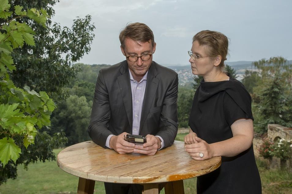Roland Wöller und seine Ehefrau Corinna Franke-Wöller verfolgen auf Gut Pesterwitz am Handy die Zwischenstände am Wahlabend.