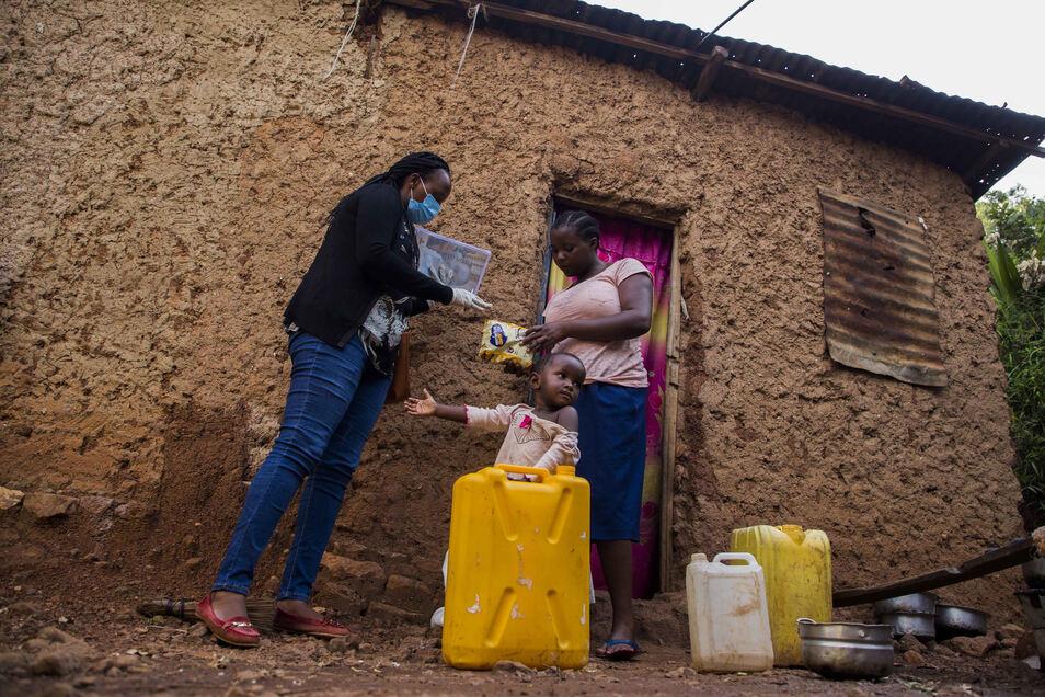 Corona auch in Kigali, der Hauptstadt von Ruanda: Eine Beamtin übergibt einer Familie Hilfsgüter.