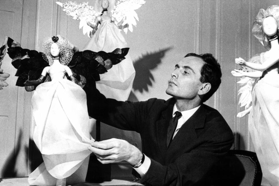 """Pierre Cardin präsentiert im Jahr 1958 festlich gekleidete Puppen, die in der Vorweihnachtszeit an den Wänden seines Salons aufgestellt wurden und die seine neuesten Kreationen im """"Kleinformat"""" trugen."""