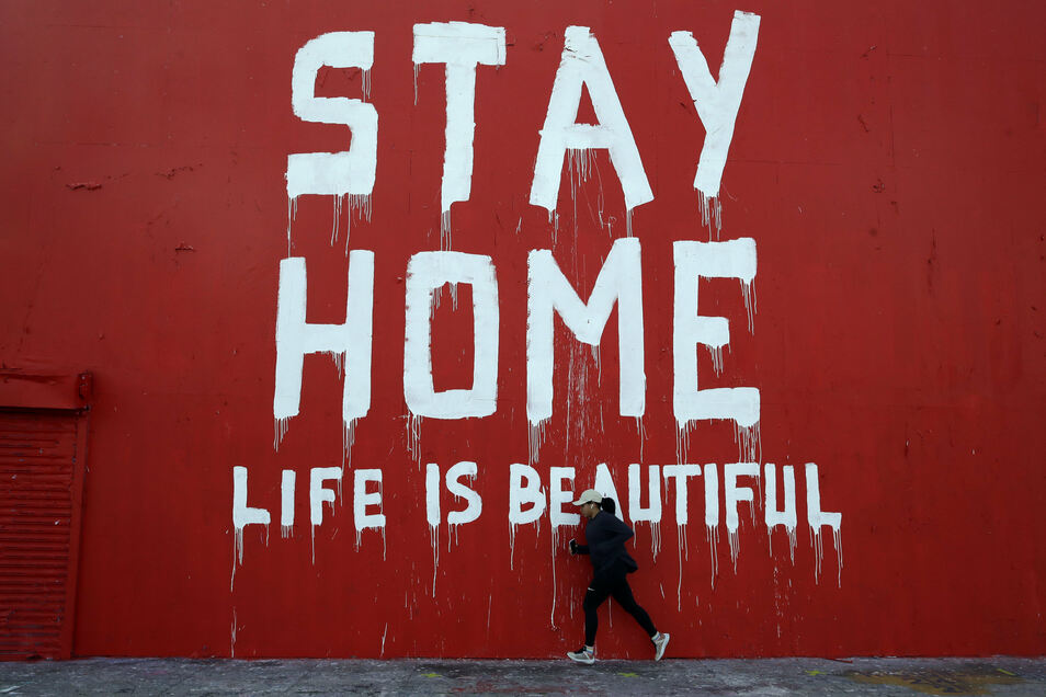 """USA, Los Angeles: Ein Jogger läuft an einem Wandbild mit der Aufschrift """"Stay Home - Life is beautiful"""" (""""Bleib zu Hause, das Leben ist schön"""") vorbei."""