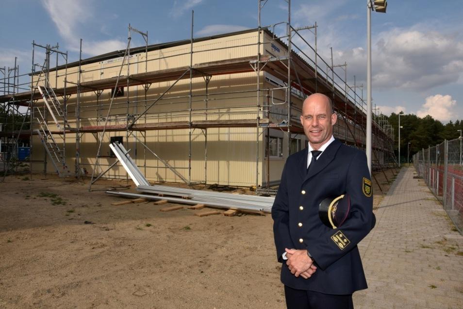 Markus Morgenstern ist seit Mai Leiter der Landesfeuerwehr- und Katastrophenschutzschule in Nardt. Er steht hier neben dem Sportplatz vor dem provisorischen Internatsgebäude, das gerade aus Wohncontainern entsteht.