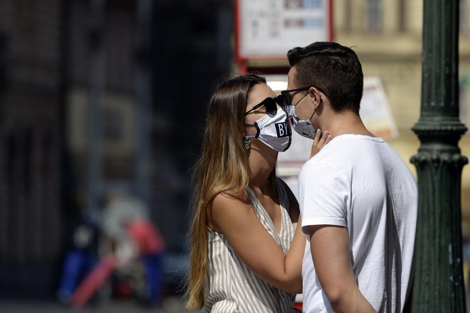 Tschechien, Prag: Ein junges Paar mit Mundschutz schaut sich in die Augen auf dem Friedensplatz.