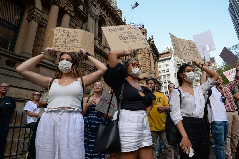 """Demonstranten halten Plakate hoch. Die von Studierenden organisierte """"Sack ScoMo!""""-Klimakundgebung macht auf den Zusammenhang der verheerenden Buschbrände mit dem Klimawandel aufmerksam."""