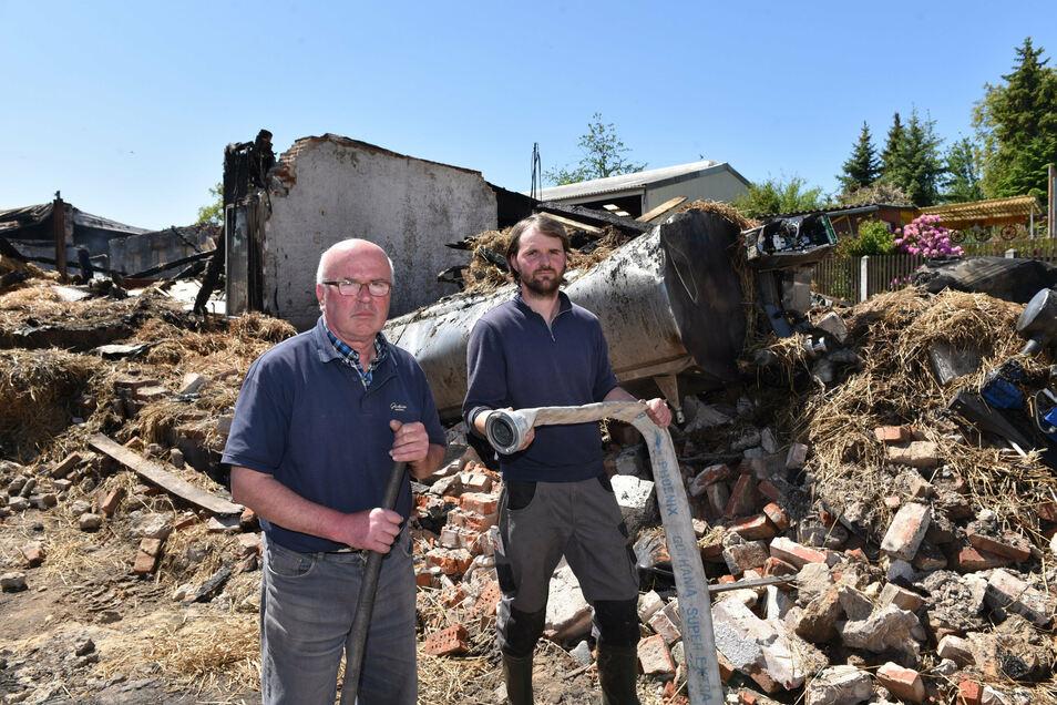 Hubertus (li.) und Alexander Schroth vor den Resten der nagelneuen Melkanlage, die bei dem Großbrand der Scheune Ende Mai mit vernichtet wurde.