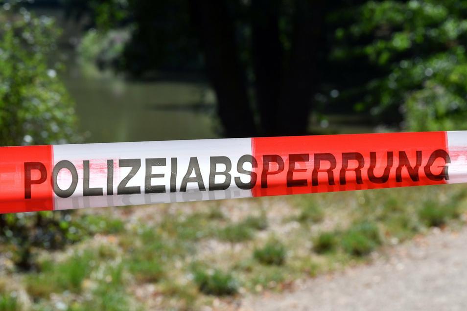 Absperrband der Polizei sichert den Inselteich im Clara-Zetkin-Park. Hier war am 6. August die Leiche eines 68-Jährigen gefunden worden. Der Mann soll gewaltsam ums Leben gekommen sein.